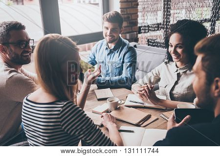 Discussing the latest news. Cheerful young people looking at each other with smile while sitting at the office table at the business meeting