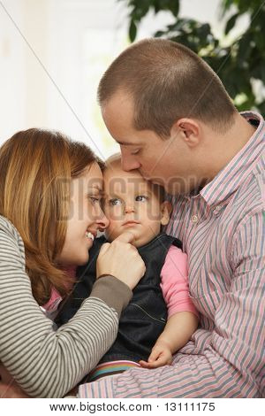 Baby girl sleeping in father's arm on sofa, father kissing on head, mother looking tenderly.?