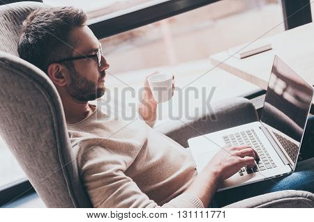 Surfing web from cafe. Side view of handsome man using his laptop and holding coffee cup while sitting in chair in front of window