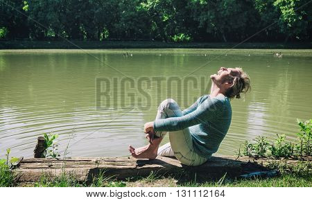 Young blonde man laughing by the river, barefoot