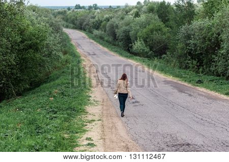Legs of young woman in casual wear walking the forest road. concept of tourism loneliness, uncertainty, choice.