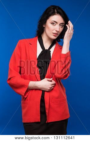 brunette in a black blouse and a red jacket on a blue background