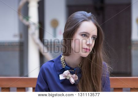 Attractive thoughtful woman with bows on neck looking away