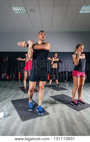 People stretching arms in fitness class on sports center