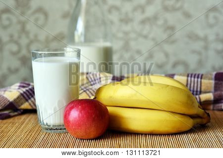 A glass and a bottle of milk apple bananas and yellow towel