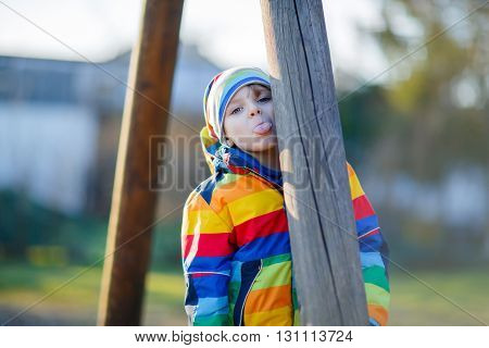 Little kid boy having fun and showing tongue on outdoor playground. child on warm sunny spring or autumn day. Active leisure with kids. Boy wearing colorful clothes