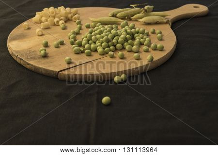 Peas beans on wooden chopping board on a black background. Ingredients for pasta and peas. Italian food Italian style.