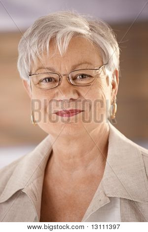Closeup portrait of happy senior woman wearing glasses, looking at camera, smiling.?