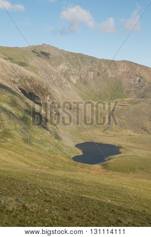 A view down grassy banks to Llyn Ffynnon y-gwas a lake below the steep flanks of the west face of Snowdon Wales UK.
