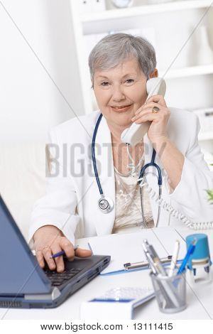 Senior female doctor, working at desk, talking on phone.?
