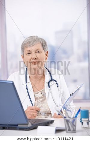 Senior female doctor, working at desk, making notes.?