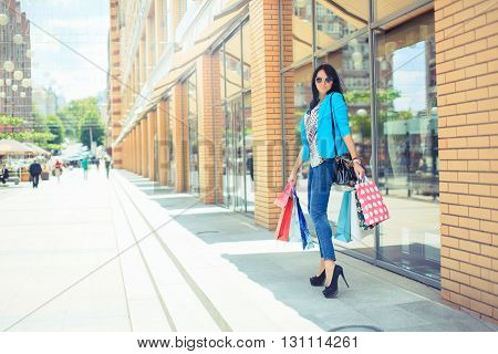 Woman stands near window shop - Young pretty girl standing in front of a boutique holding shopping paperbags