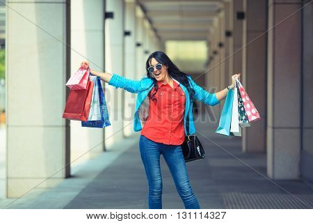 Pretty young fashion woman holding shopping bags and standing near shop window
