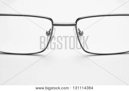 Male eyeglasses macro detail over a white background. Horizontal