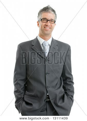 Portrait of businessman wearing gray suit and glasses, standing with hands in pocket, smiling.  Isolated on white background.