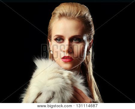 Beautiful young woman with luxury fur on dark background with blue light