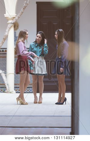 Three young elegant women making conversation standing