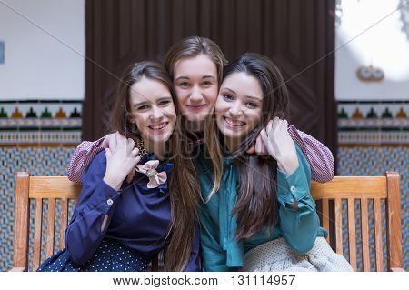 Three attractive smiling women hugging on bench and looking at camera