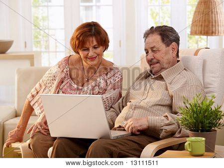 Elderly couple using laptop computer at home, looking at screen, smiling.?
