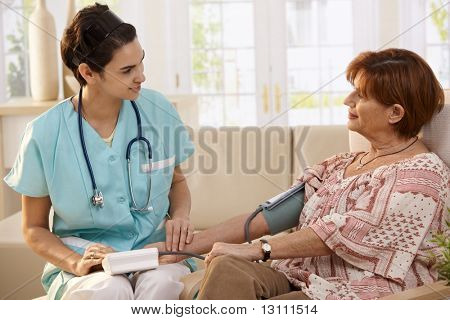 Nurse measuring blood pressure of senior woman at home. Smiling to each other.?