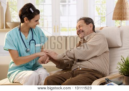 Happy nurse holding hands of elderly patient sitting side by side at home, laughing.?