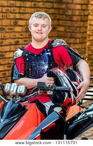 Close up portrait of young man with down syndrome sitting with sportswear and helmet on quad bike.