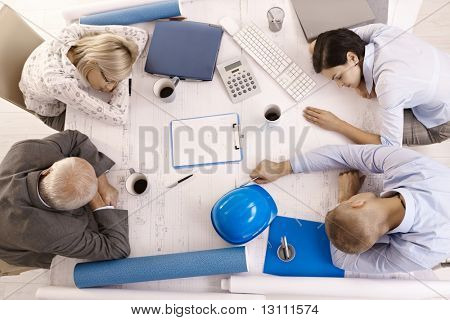 Tired businesspeople at meeting, sleeping leaning on table, high angle view.?