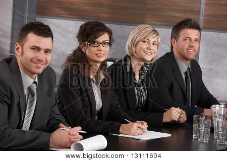 Businesspeople sitting in a row at meeting table in office, looking at camera, smiling.?