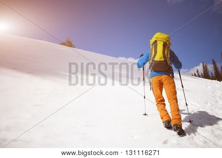 Climber With A Backpack Climbs The Snow.