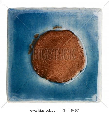 Blue handmade glazed ceramic tile with brown dot in middle isolated on white