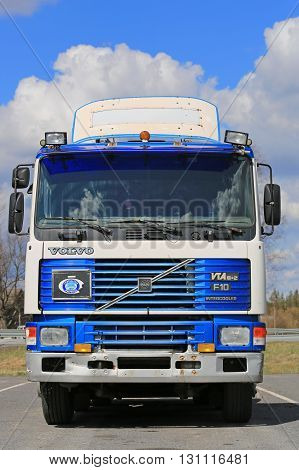 FORSSA FINLAND - APRIL 30 2016: Blue and white Volvo F10 Intercooler vta 6x2 truck tractor parked on a yard with blue sky and clouds background. The F10 was launched in 1977.