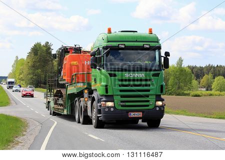 SALO FINLAND - MAY 20 2016: Green Scania R500 semi truck transports Hitachi crawler excavator along rural spring highway in South of Finland.