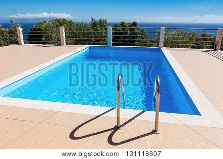 Water in blue swimming pool near sea in greece during summer season