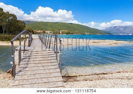 Wooden pedestrian walkway on sunny pebbles beach in greece