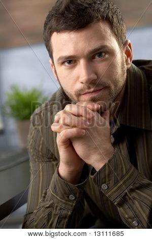 Porträt zielstrebig Mannes Blick in die Kamera, die mit Hände gefaltet im Büro sitzen.