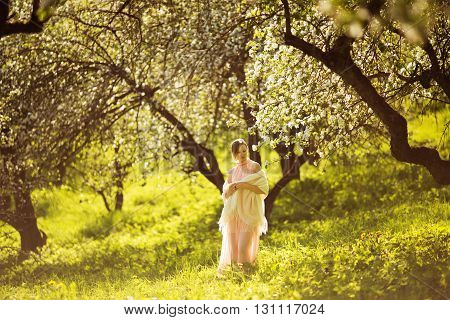 Woman in a dress are standing among apple blossom