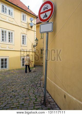 a man with a small dog walks among houses
