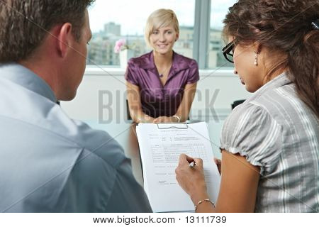 Conductors holding questionnaire form during the job interview, applicant's reults are excellent. Focus placed on sheet in front.