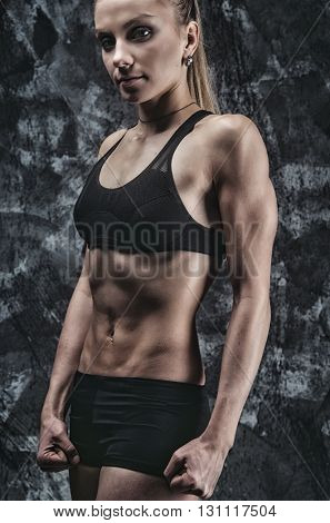 Close up image of female in sports clothing workout on grey background. Muscular female body.