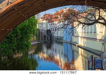 view of the narrow channel among houses in Prague in sunny spring day