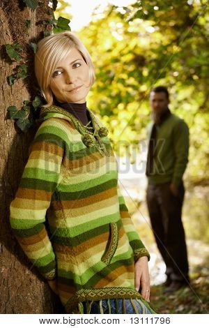 Outdoors portrait of happy young woman leaning to tree trunk in autumn park, smiling.?