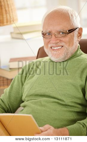 Portrait of smiling senior man wearing glasses, sitting at home holding book.?