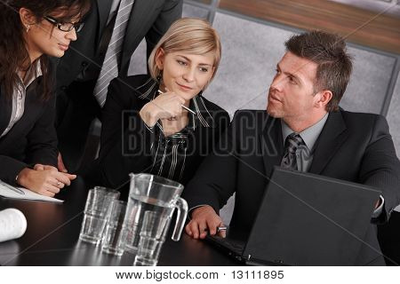 Businessman showing data on laptop computer during business meeting. Businesswomen looking at screen, thinking.?