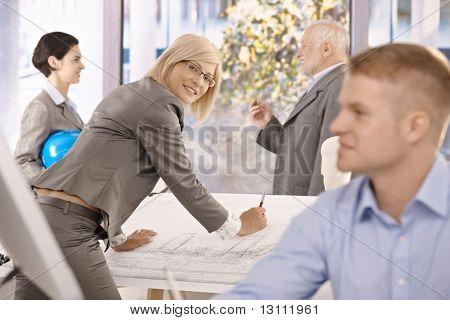Architekten arbeiten in Büro, weibliche Designer lächelnd in die Kamera, die an Plan arbeiten.?
