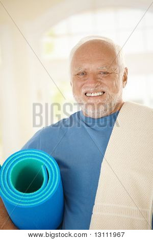 Active senior in sportswear holding polyfoam, smiling at camera.?