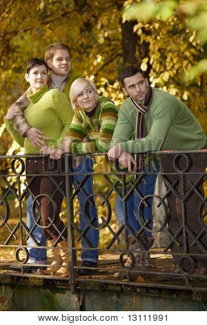 Two smiling couples standing in autumn park, leaning to railing.?
