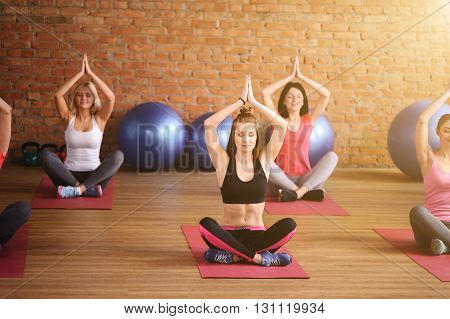 Beautiful young women are doing yoga in group. They are sitting in lotus position and raising arm up. The ladies are smiling. Their eyes are closed with relaxation
