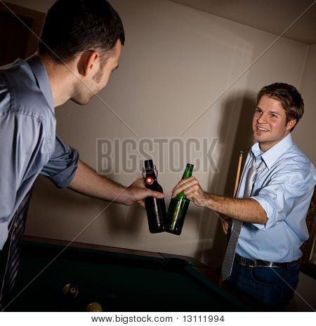 ¿Jóvenes hombres guapos tintinear botellas de cerveza en el billar, sonriendo, celebrando juego.?