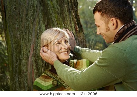 Portrait of happy couple in park, man caressing smiling woman's face.?
