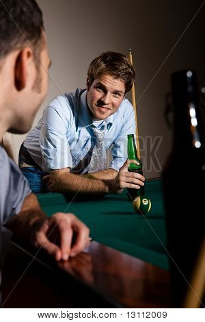 Friends chatting at snooker table, having beer, smiling.?